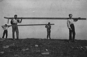 Gli uomini della vallata che portano a spalla le travi in metallo della Croce
